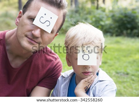Concept of positive thoughts and emotions. On the foreheads shows (drawn) worry and surprise icons. Worried father and surprising son sitting on the green grass in nature sunny day. - stock photo