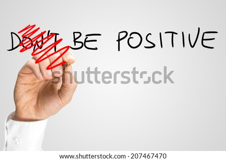 Concept of positivity and optimism - male hand changing a Don't be positive into a Be positive sign. - stock photo