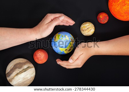 Concept of protecting Earth - with hands shielding our planet, on black background - stock photo