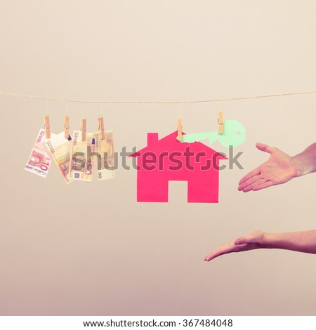 Concept of real estate and deal. Hands of seller man with house model and money banknotes. Selling and buying proposition. - stock photo