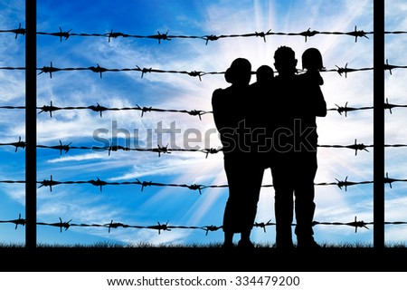 Concept of refugee. Silhouette of a family with children of refugees and fence with barbed wire