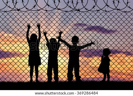 Concept of refugee. Silhouette of the hungry children of refugees near the border fence in the sunset - stock photo