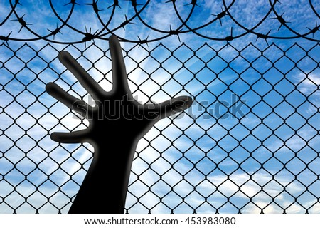 Concept of refugees. Silhouette hands refugee near the fence of barbed wire