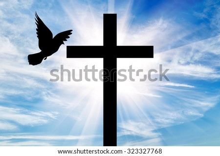 Concept of religion. Silhouette of a cross and dove in the rays of light on the background of the beautiful sky - stock photo