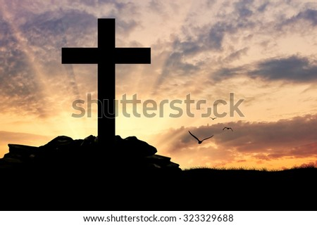 Concept of religion. Silhouette of a cross in beams of light at sunset