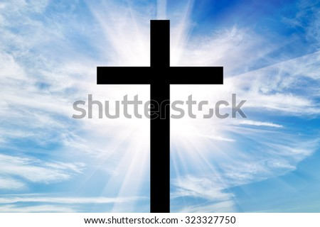 Concept of religion. Silhouette of a cross in beams of light on the background of the beautiful sky