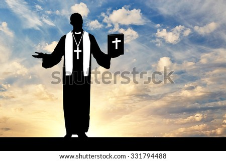 concept of religion. Silhouette of a priest praying with the Bible in his hand against the evening sky in the sun - stock photo