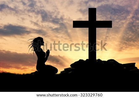 Concept of religion. Silhouette of a woman praying before the cross at sunset - stock photo