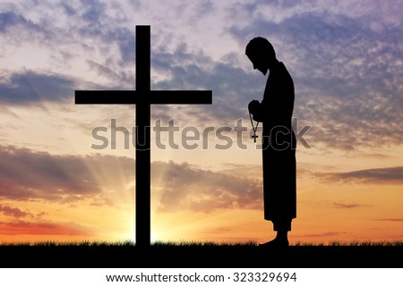 Concept of religion. Silhouette of priest and cross on a background of beautiful sky - stock photo