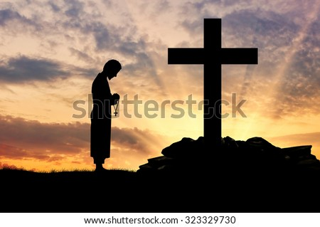 Concept of religion. Silhouette of priest and cross on a background of beautiful sky