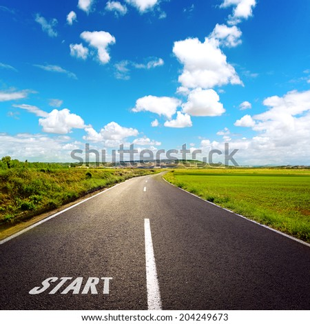 Concept of right path to progress and success. Beautiful straight asphalt road among green grass with blue sky background.