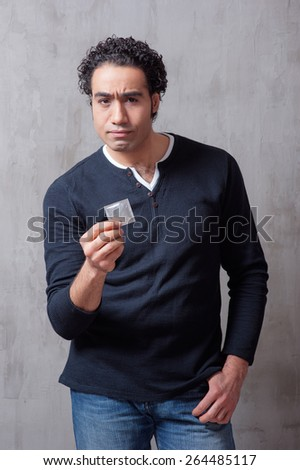 Concept of safety sex. protect your self! Handsome arabic man in casual wear holding condom while standing against grey background.