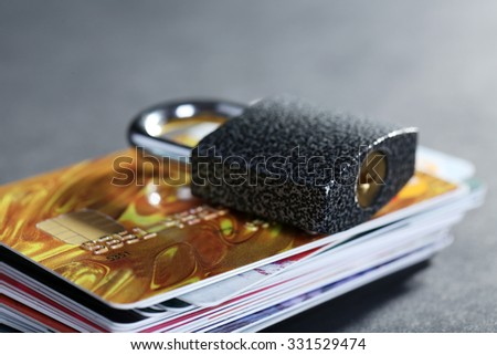 Concept of saving money - lock with credit cards on black background - stock photo