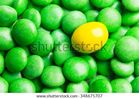Concept of selective focus on yellow chocolate candy against heaps of green candies in background