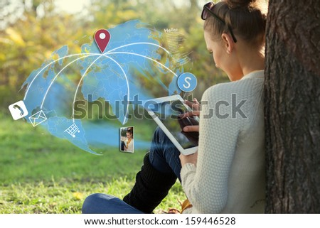 Concept of sitting young woman using her tablet pc during rest in the park - stock photo