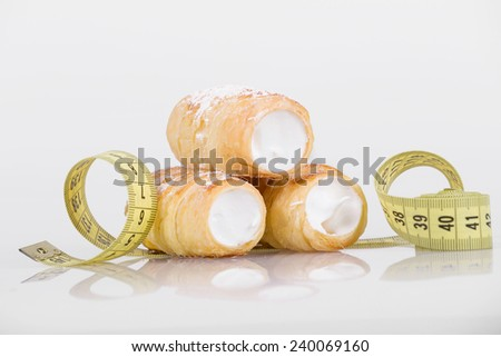 concept of slimming, cakes with measuring tape on white background