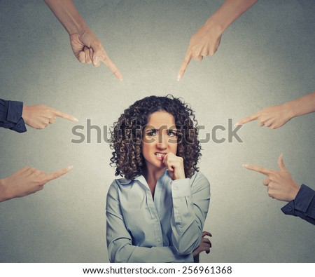 Concept of social accusation of guilty businesswoman many fingers pointing at isolated on grey office wall background. Portrait scared anxious embarrassed woman biting fingernails - stock photo