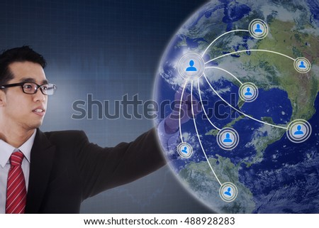 Concept of social network connection with Asian businessman pressing social network button on the virtual screen. Elements of this image furnished by NASA