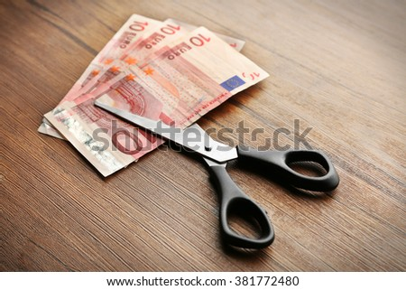 Concept of spending money - scissors cut money on wooden background - stock photo