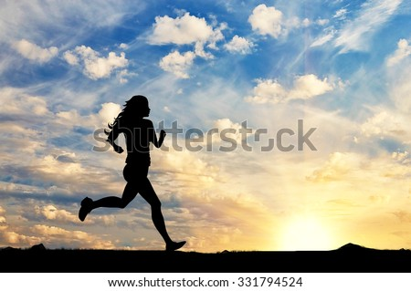 Concept of sport. Silhouette of a girl running in the background of a sunset - stock photo