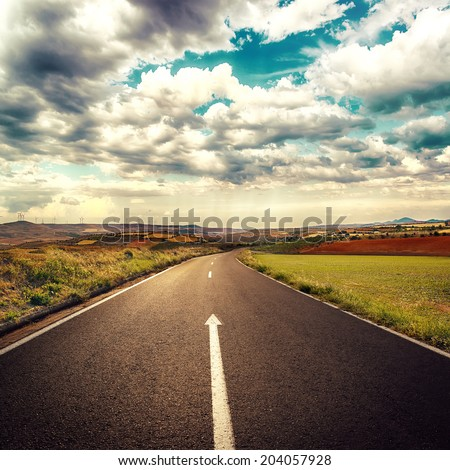 Concept of straight way for business and new career start. Asphalt road over cloudscape background.