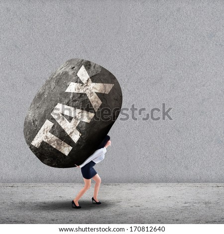 Concept of stress of a businesswoman carrying a big rock of TAX - stock photo