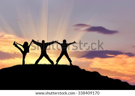 Concept of success. Silhouette of three happy people on top of the mountain against the evening sky