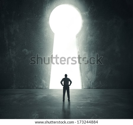 Concept of success with businessman looking through key hole - stock photo