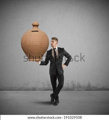 Concept of success with businessman that holds a piggy bank - stock photo