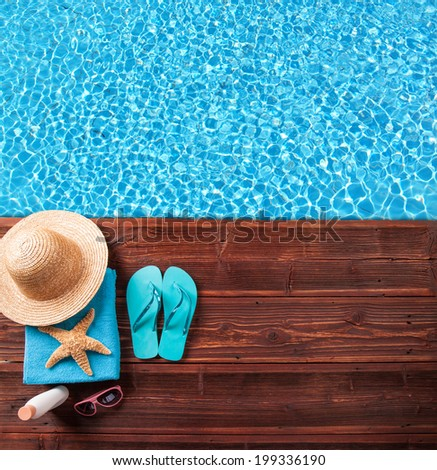 Concept of summer accessories on wood with blue water - stock photo