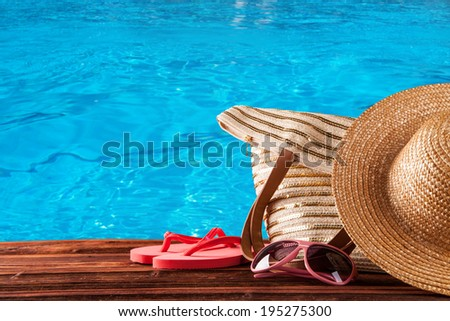 Concept of summer accessories on wood with blue water as background - stock photo