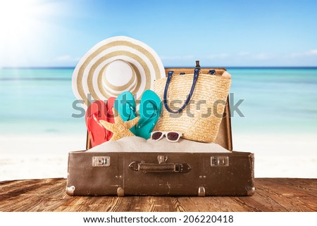 Concept of summer traveling with old suitcase and accessories. Blur beach on background - stock photo
