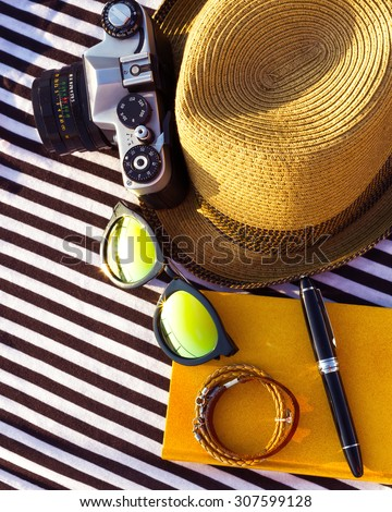 Concept of summer travelling with retro camera and accessories. Top view of summer male female accessories on vacation.Straw hat, camera, book, note book,sunglasses,bracelet and striped beach t-shirt - stock photo