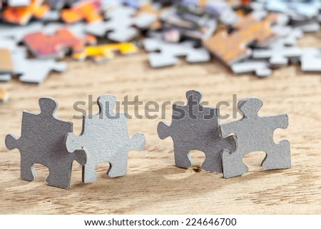 Concept of teamwork: Four jigsaw puzzle pieces on a table joint together. Shallow depth of field - stock photo