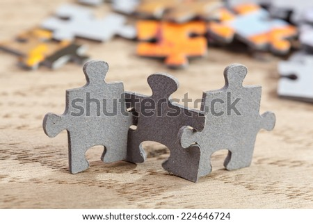 Concept of teamwork: Three jigsaw puzzle pieces on a table joint together. Shallow depth of field - stock photo