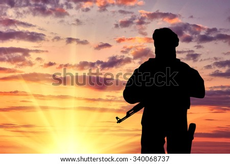 Concept of terrorism. Silhouette of a terrorist with a weapon against a background of a sunset