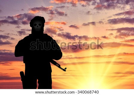 Concept of terrorism. Silhouette of a terrorist with weapons and a skull face at sunset