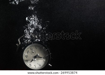Concept of time. Vintage alarm clock in water with air bubbles. Photo on black background. Plenty of space for text. - stock photo