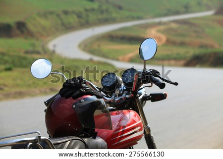 Concept of travel by motorcycle on an empty road at sunny day. Focus on the gloves. - stock photo