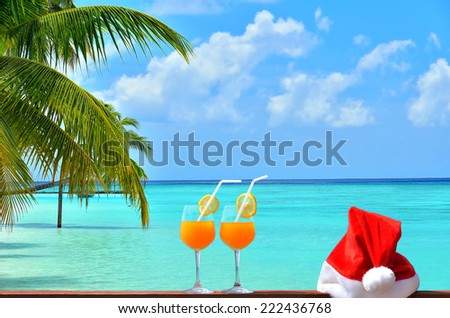 Concept of tropical christmas vacations -- Two tropical fresh juices and red santa hat near the beautiful tropical beach with palm trees - stock photo