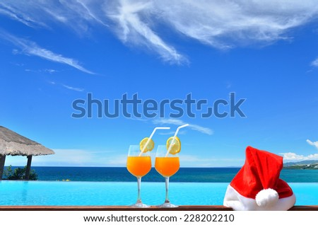 Concept of tropical christmas vacations -- Two tropical fresh juices and red santa hat near the Infinity pool - stock photo