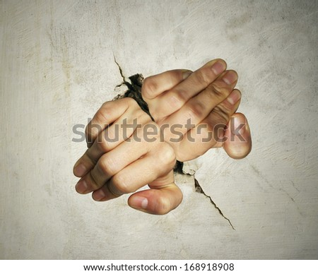 Concept of two hands trying hard to get out of breaking the wall - stock photo