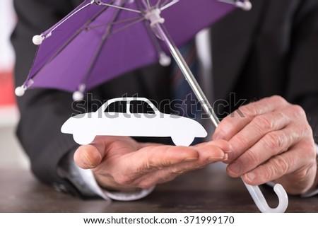 Concept of umbrella over a car - stock photo