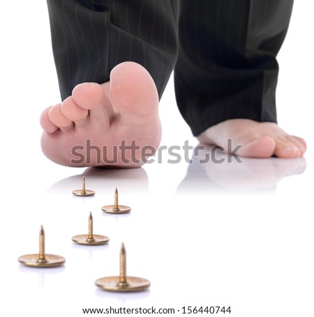 concept of unforeseen problem or danger ahead, foot stepping on a pin isolated on a white background - stock photo