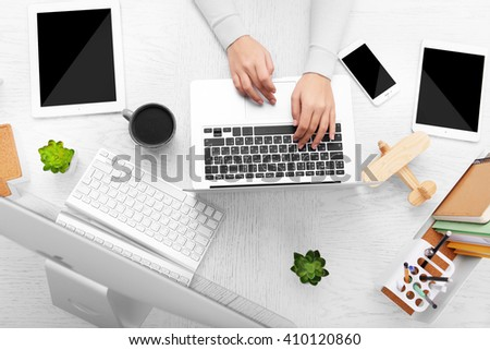 Concept of using electronics. Businesswoman works at office. Computer, laptop, tablet, cup of coffee and other things on the table. Top view - stock photo