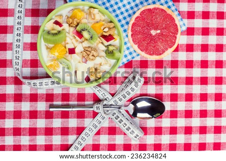 Concept of weight loss with the help of a balanced healthy diet. Vegetarian Breakfast: fruit salad with yogurt and nuts. The theme of a healthy lifestyle and balanced diet food. - stock photo