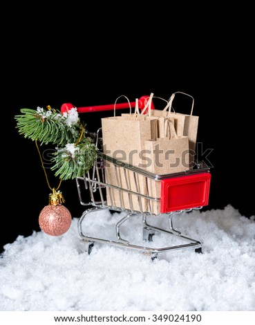Concept of winter sale. Shopping cart with paper bags and decoration is isolated on black background, closeup - stock photo