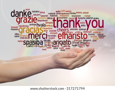 Concept or conceptual abstract thank you word cloud held in hands in different languages or multilingual for education or Thanksgiving Day over rainbow sky - stock photo