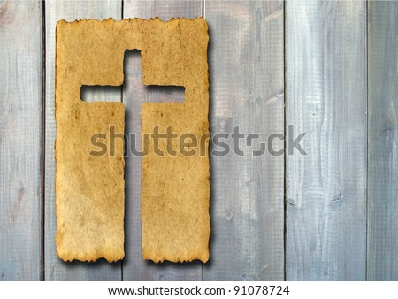 Concept or conceptual Christian cross cut in an old grungy or vintage paper, over a wood texture background for religion, retro, aged, grunge, faith, holiday, God, religious, Jesus or belief designs