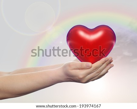 Concept or conceptual 3D red glass heart sign or symbol held in hands by a woman or child over nice rainbow sky background, metaphor to love, holiday, wedding, care, valentine, protection or romantic